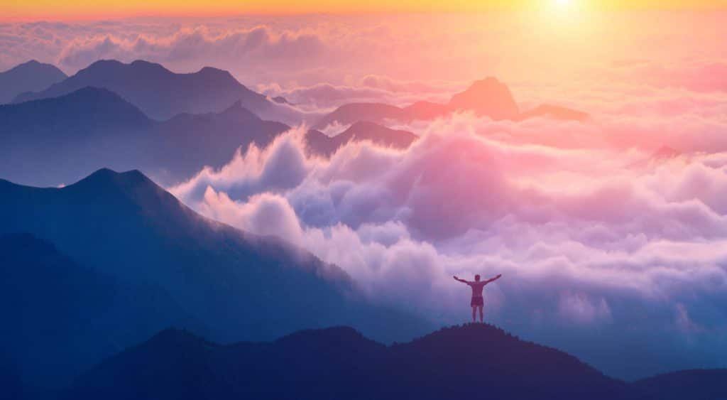 Man standing on a mountain top with rised hands and welcome sunrise in a Crimea mountains above the cloudy valley